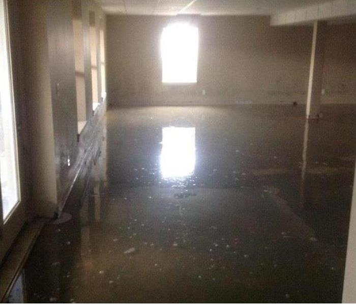 vacant building with muddy water covering the floor