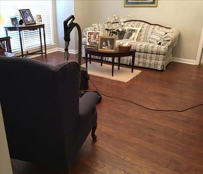 a view of the living room, no wetness, no damage, a chair, sofa, and several small tables with photos on them