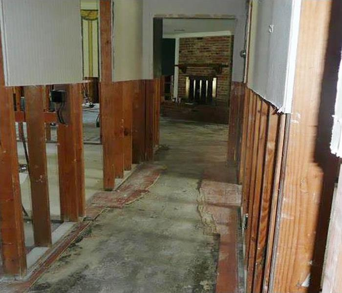 water damaged home with exposed walls and flooring removed
