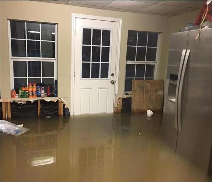 filthy floodwater covering floor and bottom of a refrigerator