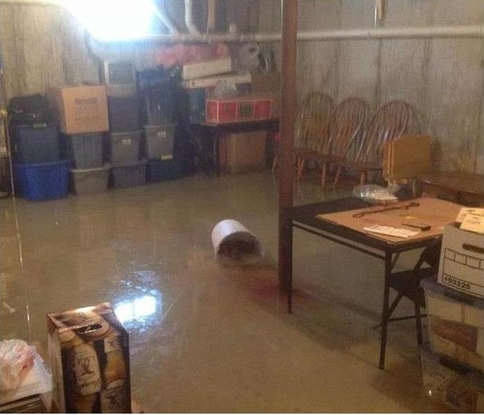 water in basement, chairs and stacked plastic containers in corner