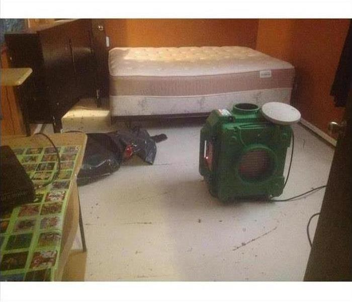 A bedroom with an air scrubber in the middle of the floor after a fire