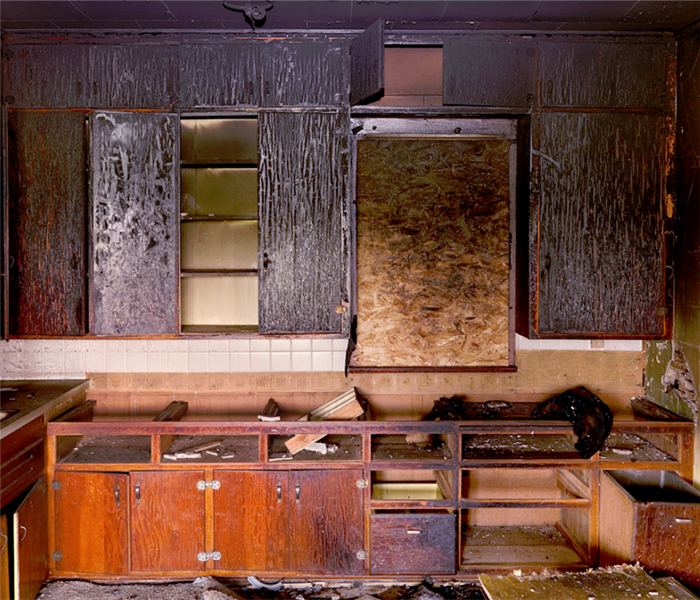 a fire damaged kitchen with soot covering everything