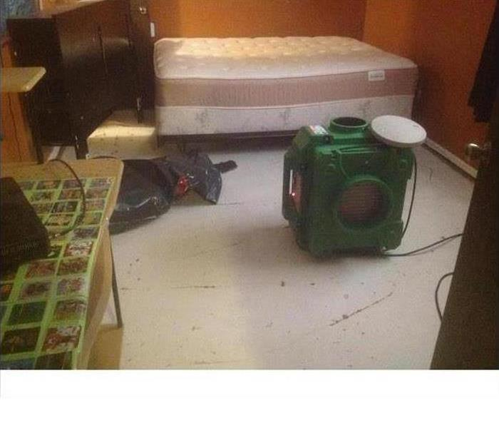 An air scrubber set up in a bedroom cleaning the air